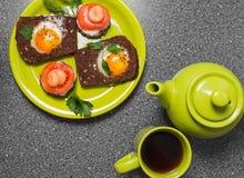 Prima colazione - pane tostato con il pomodoro del formaggio fuso, le uova fritte, le uova fritte, la teiera e la tazza di tè su  Fotografia Stock