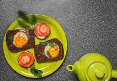 Prima colazione - pane tostato con il pomodoro del formaggio fuso, le uova fritte, le uova fritte, la teiera e la tazza di tè su  Immagini Stock Libere da Diritti