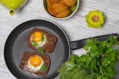 Prima colazione - pane tostato con il pomodoro del formaggio fuso, le uova fritte, le uova fritte, la teiera e la tazza di tè su  Immagine Stock