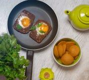 Prima colazione - pane tostato con il pomodoro del formaggio fuso, le uova fritte, le uova fritte, la teiera e la tazza di tè su  Fotografie Stock