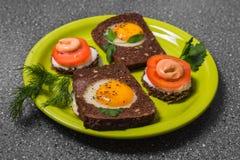 Prima colazione - pane tostato con il pomodoro del formaggio fuso, uova fritte, uova fritte, su un fondo grigio Fotografia Stock Libera da Diritti