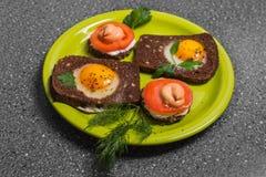 Prima colazione - pane tostato con il pomodoro del formaggio fuso, uova fritte, uova fritte, su un fondo grigio Fotografia Stock