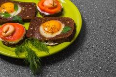 Prima colazione - pane tostato con il pomodoro del formaggio fuso, uova fritte, uova fritte, su un fondo grigio Immagine Stock Libera da Diritti