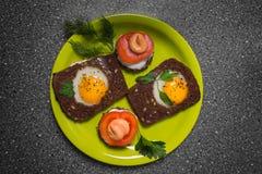 Prima colazione - pane tostato con il pomodoro del formaggio fuso, uova fritte, uova fritte, su un fondo grigio Immagini Stock