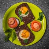 Prima colazione - pane tostato con il pomodoro del formaggio fuso, uova fritte, uova fritte, su un fondo grigio Fotografie Stock Libere da Diritti