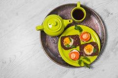 Prima colazione - pane tostato con il pomodoro del formaggio fuso, uova fritte, uova fritte, tazza della teiera di tè su un fondo Fotografie Stock