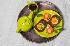 Prima colazione - pane tostato con il pomodoro del formaggio fuso, uova fritte, uova fritte, tazza della teiera di tè su un fondo Immagine Stock