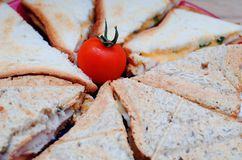 Prima colazione: panini con formaggio ed il prosciutto, decorati con i pomodori ciliegia Fotografia Stock