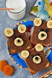 Prima colazione per i bambini - pane tostato con la pasta del cioccolato, banana e fotografie stock