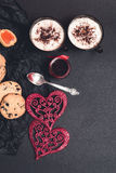Prima colazione romantica due tazze di caffè, cappuccino con i biscotti del cioccolato e biscotti vicino ai cuori rossi sul fondo Fotografie Stock