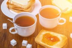 Prima colazione romantica per due con la tazza della marmellata di amarene calda e del tè con pane e burro tostati Fotografia Stock