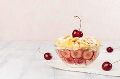 Prima colazione rosa molle con i fiocchi di mais dorati, ciliege mature, zucchero in polvere sul bordo di legno bianco con lo spa Immagine Stock