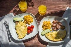 Prima colazione rustica dell'omelette, della salsiccia, del korn e del pomodoro Fotografie Stock