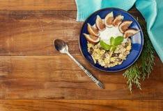 Prima colazione sana con i muesli, il yogurt ed i fichi sulla tavola di legno Fotografia Stock Libera da Diritti