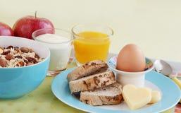 Prima colazione sana con l'uovo, il pane, il formaggio, il yogurt ed i cereali Fotografia Stock Libera da Diritti