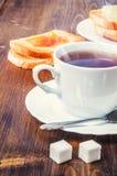 Prima colazione sana con la tazza di tè, di pane, di burro e di inceppamento Immagine Stock