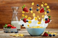 Prima colazione sana con latte, fiocchi di mais volanti, fragole immagine stock