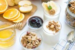 Prima colazione sana con yogurt in vetro, in granola ed in frutti Immagine Stock Libera da Diritti