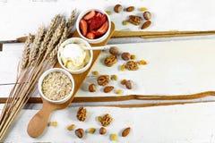 Prima colazione sana degli ingredienti - farina d'avena, yogurt, fragole - concetto di dieta e di salute, dadi ed uva passa, punt immagine stock libera da diritti