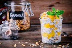 Prima colazione sana del vegano, budino di chia con il mango e granola nel barattolo su fondo di legno fotografia stock