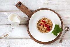 Prima colazione sana di estate di granola, muesli con la brocca di latte con la decorazione del ribes sul bordo di legno Vista su Fotografie Stock Libere da Diritti