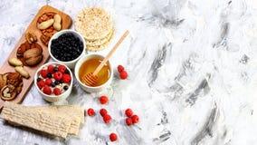 Prima colazione sana e saporita con crispybread, le bacche, il miele ed i dadi, su un fondo leggero Disposizione piana Copi lo sp immagine stock libera da diritti