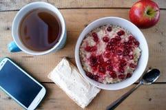 Prima colazione sana, vegetariano Farina d'avena con i mirtilli rossi, mela, panino con formaggio cremoso, tè, telefono cellulare Immagine Stock