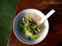 Prima colazione tailandese, congee del riso misto con carne immagini stock