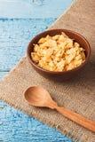 Prima colazione: un piatto dei fiocchi di granturco asciutti in un piatto dell'argilla Immagini Stock