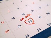 Prima data di rosso segnata alla data prestabilita bianca di ordine del giorno del calendario per romance e la datazione immagini stock
