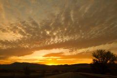 Prima degli insiemi del sole dietro le montagne Immagini Stock