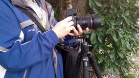 Prima del fotografo prende le immagini con la macchina fotografica di DSLR video d archivio