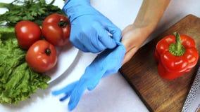 Prima della cottura il cuoco unico delle verdure mette sopra i guanti di gomma su entrambe le mani stock footage