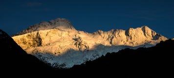 Prima luce dorata sul picco di montagna Fotografia Stock