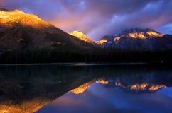 Prima luce solare sulle parti superiori della montagna Fotografia Stock
