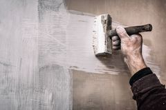 A prima mestra uma parede da massa de vidraceiro antes de aplicar uma camada decorativa de emplastro, reparos trabalha na casa, s fotografia de stock