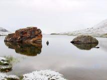 Prima neve nel lago alpino Lago autumn in alpi con il livello dello specchio ed erba e massi nevosi intorno Picchi taglienti nebb Fotografia Stock Libera da Diritti