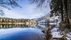 Prima neve nel lago della montagna Immagine Stock