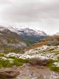 Prima neve nella regione turistica delle alpi Prato verde fresco con la corrente delle rapide Picchi delle montagne delle alpi ne Immagine Stock