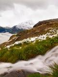 Prima neve sul prato alpino, cascata sulla corrente Picchi delle montagne delle alpi nel fondo L'acqua spumosa sta correndo giù s Fotografia Stock Libera da Diritti