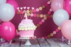 Prima torta di compleanno con un'unità su un fondo rosa con le palle e la ghirlanda di carta immagini stock libere da diritti