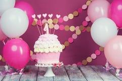 Prima torta di compleanno con un'unità su un fondo rosa con le palle e la ghirlanda di carta immagini stock