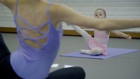 Primaballerina undervisar flickan hur man sträcker benet i den moderna ljusa studion stock video