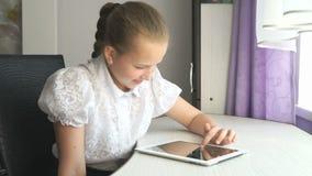 Primair schoolmeisje die een digitale tabletcomputer met behulp van stock videobeelden