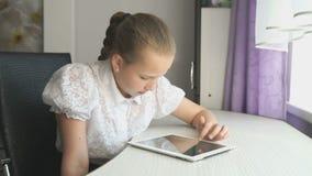 Primair schoolmeisje die een digitale tabletcomputer met behulp van stock footage