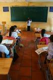 Primaire leerling die op bord in schooltijd schrijven Stock Foto