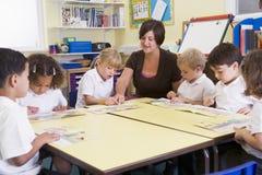 primar учитель ребенокев школьного возраста чтения их стоковое изображение