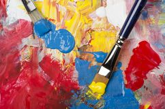 Palette with acrylic primary colors. Primary acrylic colors on a dirty palette with a spatula and brushes royalty free stock image