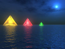 Primary Beacons. Three multi-coloured, pyramid light beacons sit silently in the sea as an intense moon assists their efforts Royalty Free Stock Photos