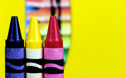 Primary Color Crayons. Three crayons in the primary colors of blue, yellow and red with box of crayons softly blurred on yellow background stock image